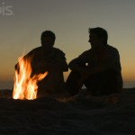 Silhouettes of Two Young Men at Campfire on the Beach